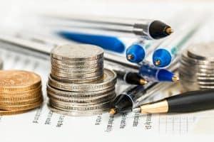 מטבעות ועט על גבי מסמך